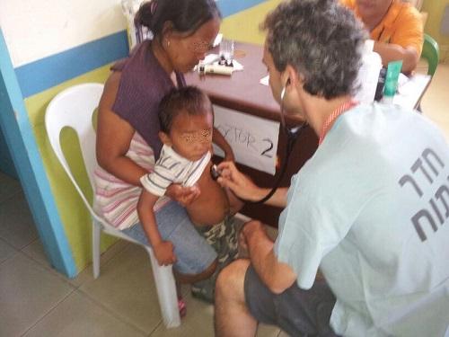 """ד""""ר דניאל גרופל, במהלך טיפול בבית חולים שדה בפיליפינים (צילום: פרטי)"""