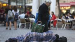 אשה חולפת על פני חסר בית, בירושלים; נובמבר 2013 (צילום: נתי שוחט / פלאש 90)