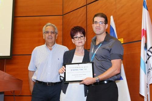 """משמאל: פרופ' עמוס עציוני והגב' ברוריה גרנדיר מעניקים את פרס החוקר הצעיר לד""""ר אודי נוסינוביץ (צילום: פיוטר פליטר)"""