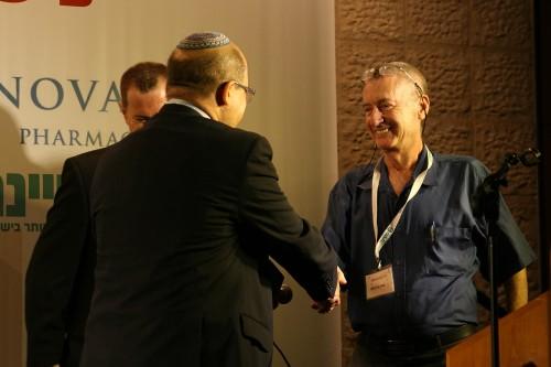 """פרופ' אהרן גליל מקבל את הפרס בפרופ' עמנואל תירוש במהלך כנס העמותה להתפתחות הילד ושיקומו (צילום: יח""""צ)"""