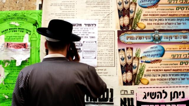 גבר עומד מול לוח מודעות בשכונת מאה שערים בירושלים; למצולם אין קשר לכתבה (צילום: אילוסטרציה)